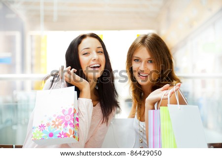 Two excited shopping woman together inside shopping mall laughing and gossip. Horizontal Shot