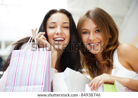 Two excited shopping woman together inside shopping mall, surprised about low prices and sales before christmas and boxing day. Horizontal Shot
