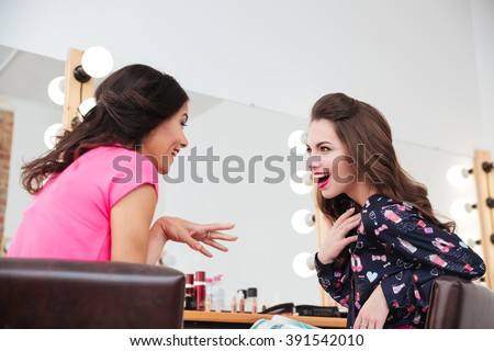 Two excited wondered young women talking near the mirror in beauty salon