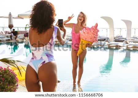 Two excited young girlfriends taking pictures while posing at the swimming pool resort spa