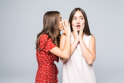 Two excited young girls dressed in summer clothes whispering secrets isolated over white background