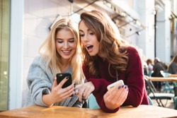 Two excited young girls using mobile phones while sitting at the cafe outdoors and pointing finger