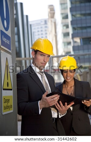 Two executives, one man and one women, wearing hard hats review plans in a modern city environment. The focus is primarily on the man in the foreground.
