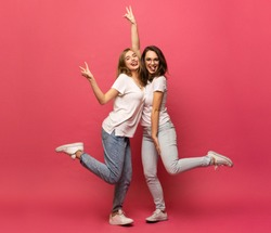 Two exited woman having fun and raising hands up. Standing on pink background. Lucky mood