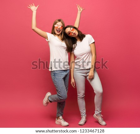 Two exited woman having fun and raising hands up. Standing on pink background. Lucky mood #1233467128