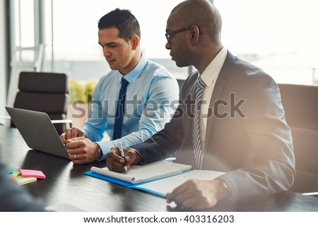 Two experienced business executives in a meeting seated at a table discussing paperwork and information on a laptop computer, one Hispanic, one African American