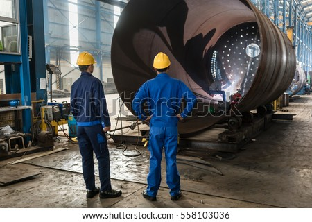 Two experienced workers supervising the manufacture of a metallic cylinder in the interior of a factory