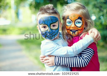 two face painted little friends embracing outside