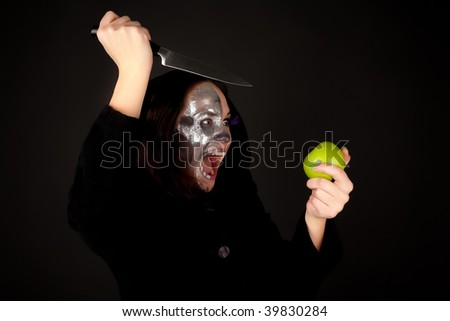 Two-faced witch with green apple and knife screaming