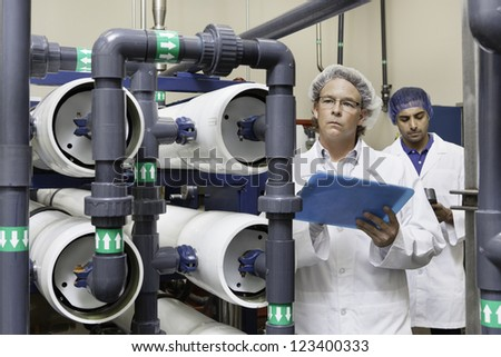 Two factory workers inspecting at bottling plant