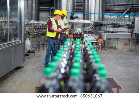 Two factory workers monitoring cold drink bottles on production line at drinks production plant
