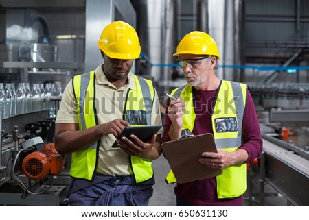 Two factory workers with clipboard and digital tablet working at drinks production plant