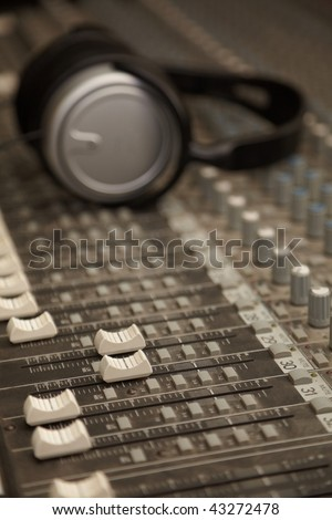 two faders of old dirty sound mixer in focus. headphones in out of focus