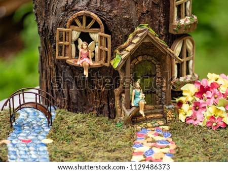 Two fairys sitting in front of their fairy house