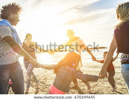 Two families playing with children on the beach - Diverse culture people having fun on summer vacation on sunset - Travel,parenthood,holidays concept - Focus on man with back sun light