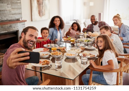 Two Families Taking Selfie As They Enjoy Meal At Home Together Photo stock ©