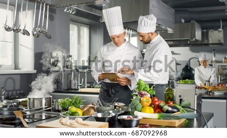 Two Famous Chefs Discuss Their Video Blog while Using Tablet Computer. They Work on a Big Restaurant Stainless Steel Professional Kitchen. #687092968