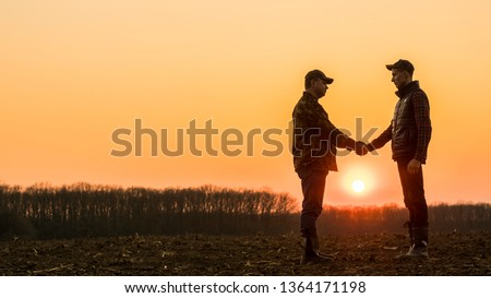 Two farmers on the field shake hands at sunset #1364171198