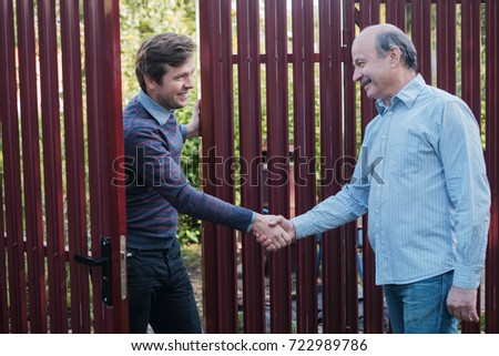 two farmers shaking hands and takling to each other on sunny day