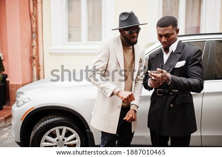 Two fashion black men stand near business car and look at cell phone. Fashionable portrait of african american male models. Wear suit, coat and hat. Stock photo ©