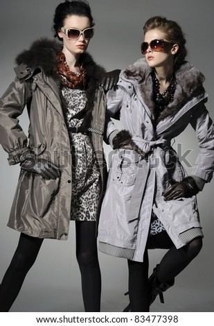 Two fashion model in autumn/winter clothes wearing sunglasses posing gray background