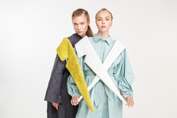 Two fashion models girls pose in stylish clothes from the spring-summer collection. Haute couture fashion. Studio portrait on a white background.