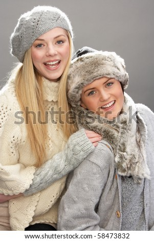 Two Fashionable Teenage Girls Wearing Cap And Knitwear In Studio In Front Of Christmas Tree