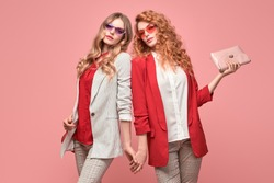 Two fashionable woman sisters in trendy autumn red outfit, stylish hair, makeup. Beautiful friends in jacket with handbag on pink. Model girl in stylish pants, fashion trend accessories, make up