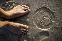 Two feet and the trace of beach soccer ball on the sand