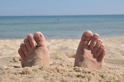 Two feet buried in sand