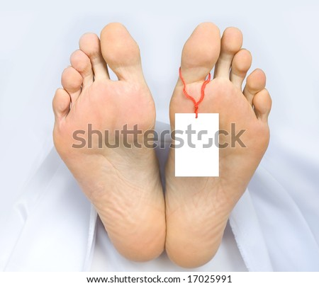 Two feet of a dead body, with an identification tag - blank sign  attached to a toe. Covered with a white sheet.