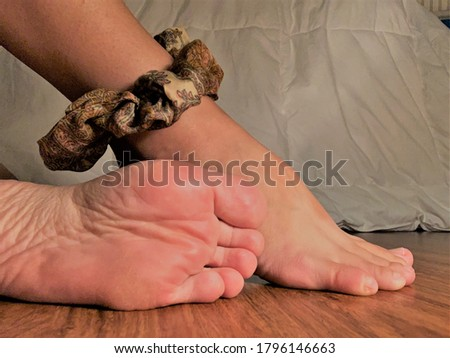 Two feet posed one underside facing camera in front of the other wearing a patterned scrunchy flexed upward on a wooden floor.