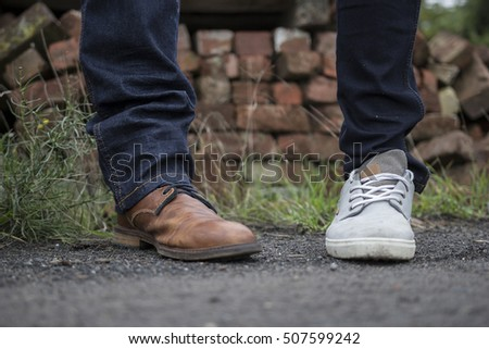 Two feet with different shoes,but both with blue jeans, standing next to each other. One shoe is rather classy, the other is more casual.The background is a pile a bricks, with grass and rough asphalt