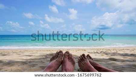 Two feets women and men on the beach with beautiful blue azul sea.