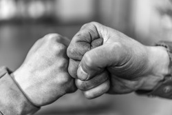 Two fellow workers greeting each other with a handshake using their fists as a symbol of companionship, friendship and solidarity.