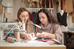 two femail Dressmakers or tailors or fashiondesigners or seamstresses woman working with sewing machine atv workshop studio. Small handmade business concept