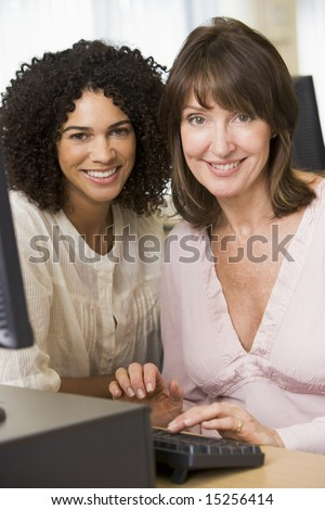 Two female adult students working on a computer together
