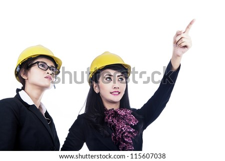 Two female architects wearing yellow helmet isolated in white