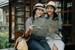 two female asian tourist with paper map sitting in bench by japanese style garden wooden house. Beautiful smiling girl friends traveler holding guide in hands discussing while travel kyoto japan