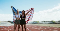 Two female athletes celebrating victory holding american flag on running track. Happy women athlete screaming in joy holding the US flag behind them at stadium.