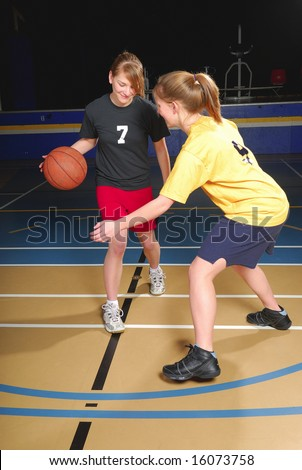 Two female basketball players compete in gym