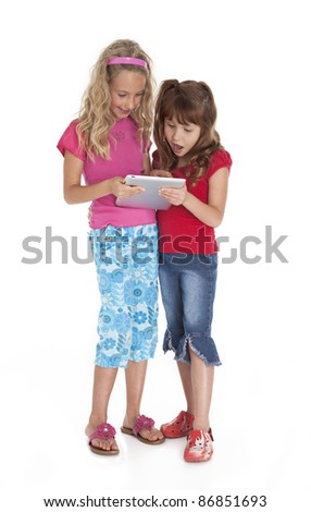 Two female children standing, holding, and looking at tablet device.