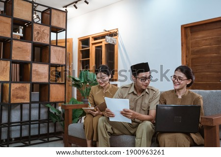 two female civil servants and a male civil servant sit using laptop computers and worksheets while working from home