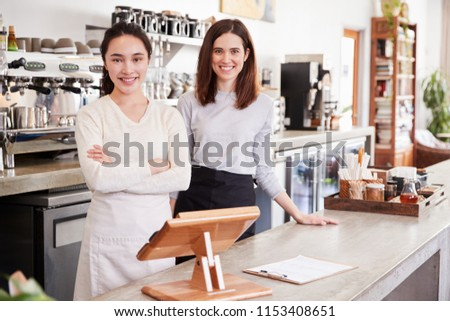 Two female coffee shop owners smiling behind counter #1153408651