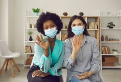 Two female colleagues, coworkers, modern vloggers, presenters or friends wearing masks waving hello at camera. Webcam portrait for video call greeting and dialogue during coronavirus pandemic lockdown
