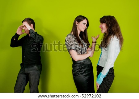 Two female colleagues gossiping and man holding his head in disbelief