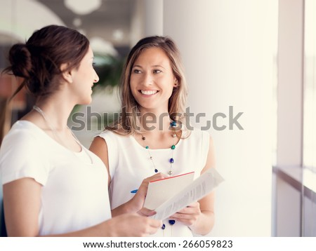 Two female collegues standing next to each other in an office #266059823