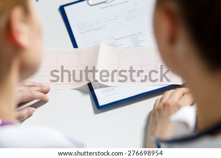 Two female doctors examining patient cardiogram chart. Professional conversation, council of cardiologists. Working conference. Medical concept