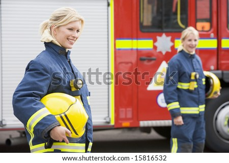 stock photo : Two female firefighters by a fire engine