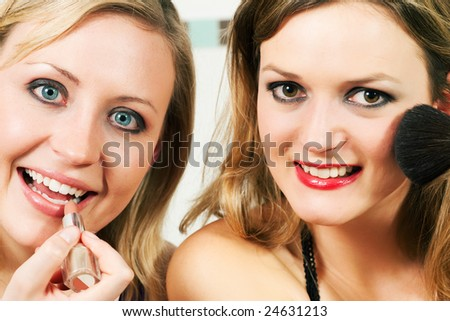 Two female friends applying lipstick and make-up with a brush - presumably to get ready for a party
